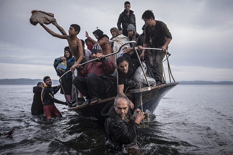 In this Nov. 1, 2015 photo by Sergey Ponomarev, migrants arrive by a Turkish boat near the village of Skala, on the Greek island of Lesbos. (AP Photo)
