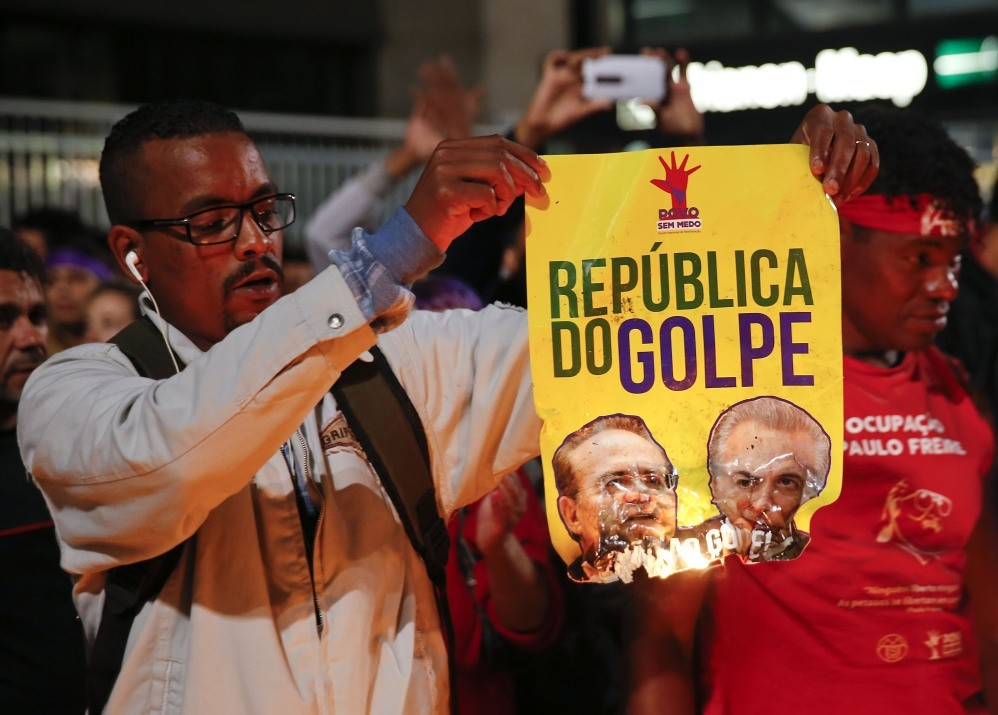 A demonstrator set fire to a poster that reads: ,Coup Republic,, during a protest in support of Brazil's suspended President Rousseff.