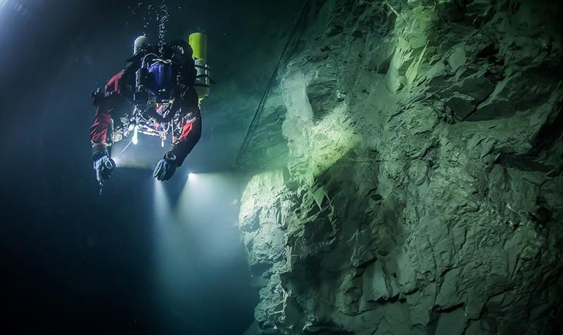 In this underwater photo taken Aug. 21, 2015, in the flooded Hranicka Abyss, Czech Republic, Polish explorer Krzysztof Starnawski is seen examining the limestone crevasse (AP Photo)