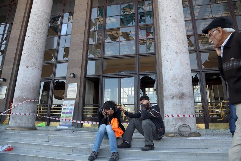 Survivors of the Oct 10, 2015 bombing sit in front of the damaged front facade of Ankara train station. (DHA Photo)