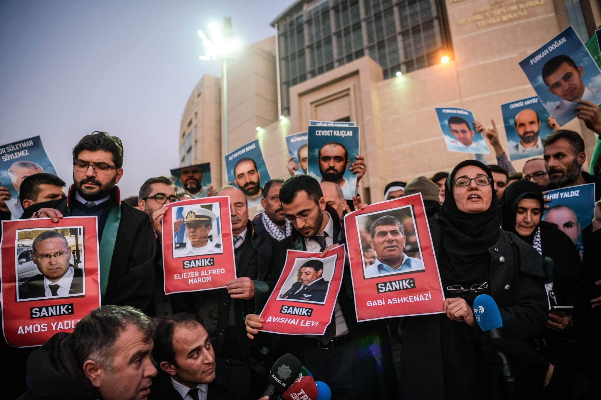 Lawyers hold pictures of accused ex-Israeli army officers as families (back) hold pictures of victims on December 9, 2016 outside the Istanbul courthouse. (AFP Photo)