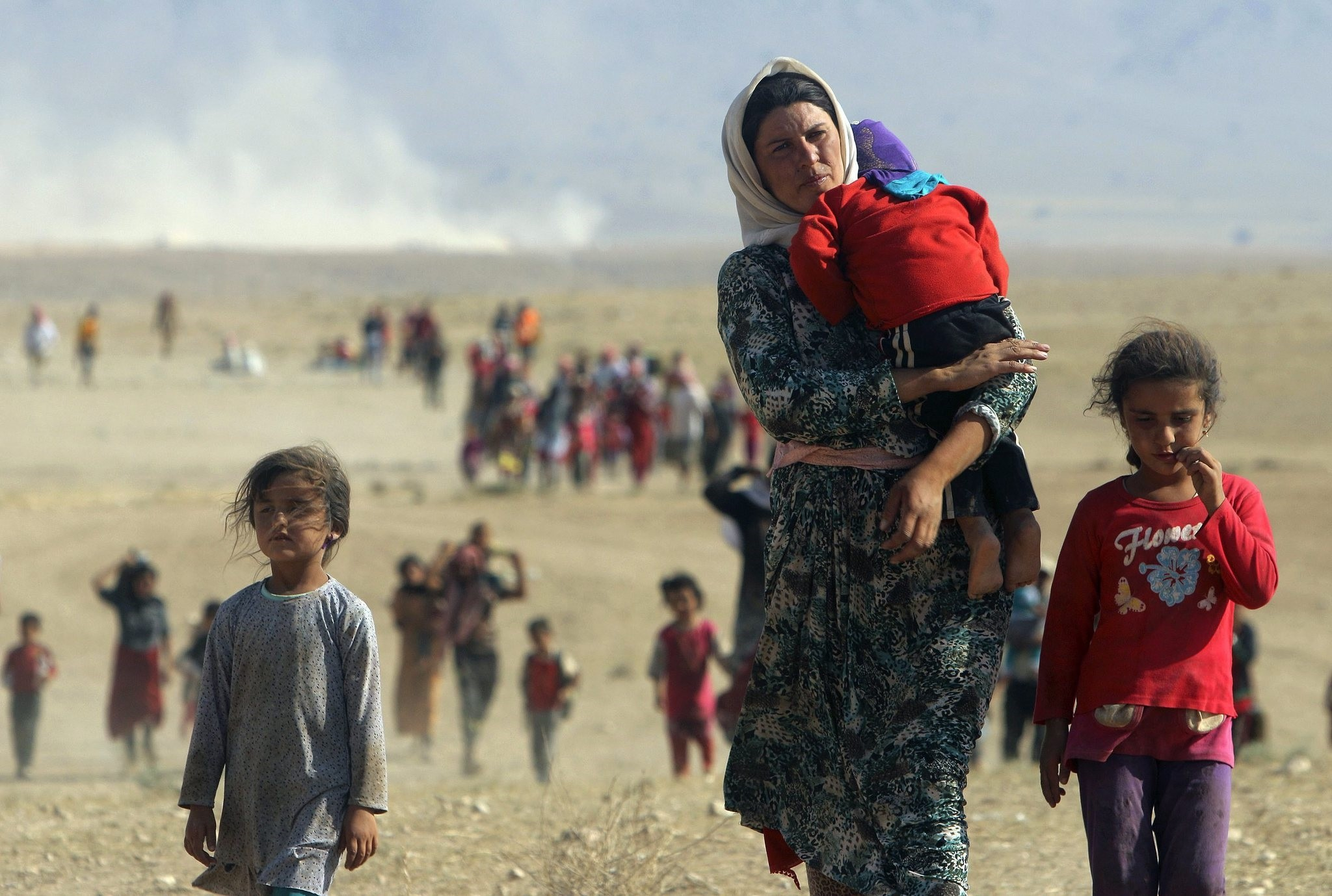 Displaced people from the minority Yazidi sect, fleeing violence from forces loyal to the Islamic State in Sinjar town, walk towards the Syrian border on the outskirts of Sinjar mountain. (REUTERS Photo)