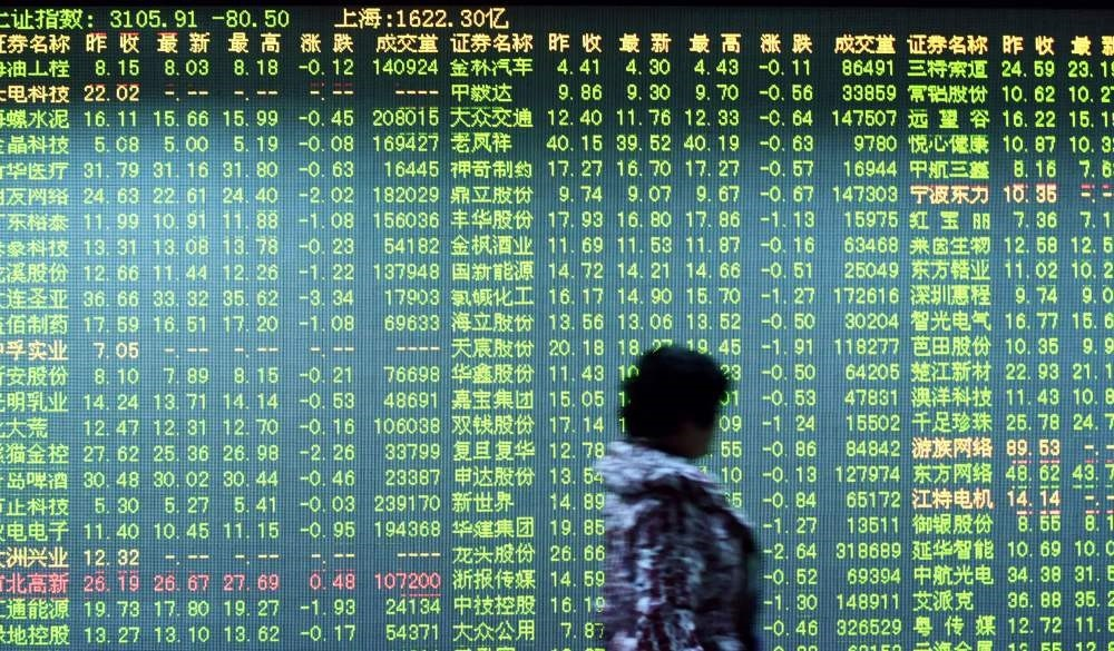 An investor walks past a screen showing stock market movements at a securities firm in Hangzhou in eastern Chinau2019s Zhejiang province.