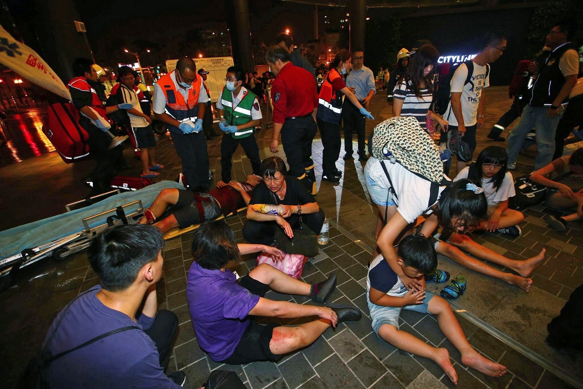 Injured people are helped by emergency rescue workers outside a station after an explosion on a passenger train in Taipei, Taiwan, Thursday, July 7, 2016. (AP Photo)