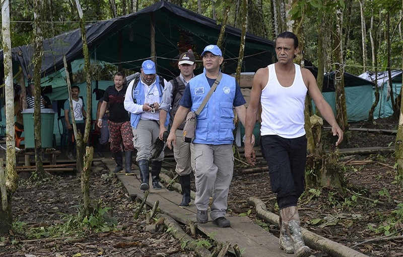 FARC guerrilla commander Pedro (R) walks with members of the United Nations Observation Mission during thier visit at the Front 34 Alberto Martinez encampment (AFP Photo)