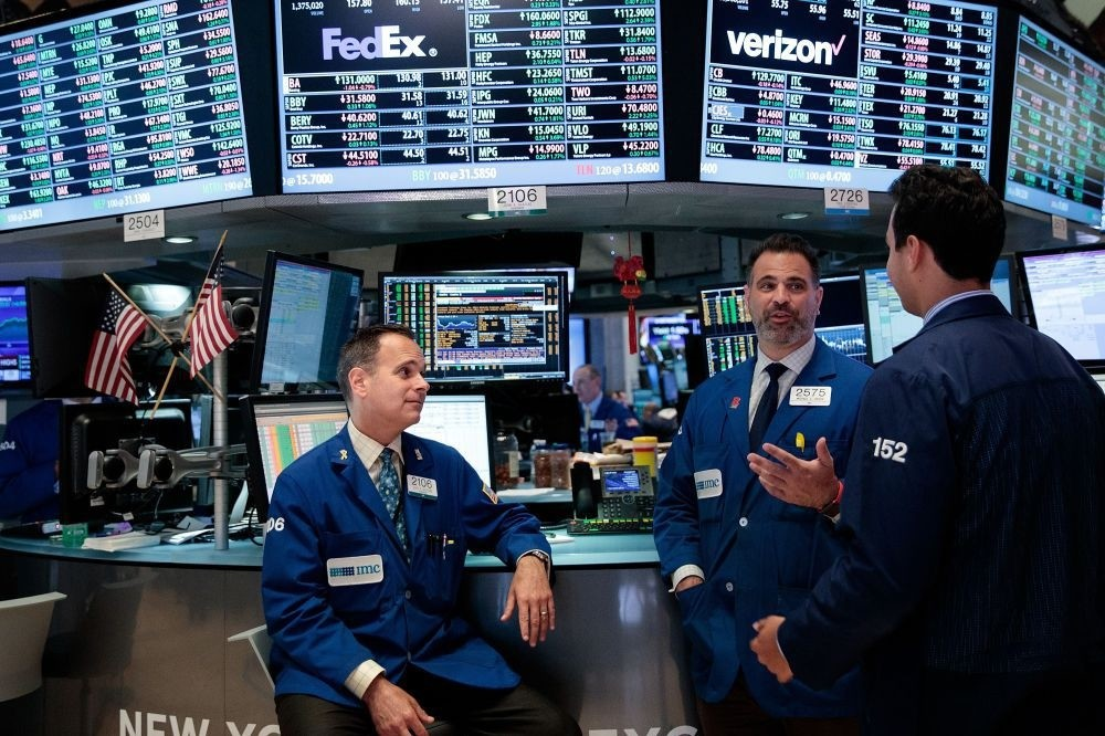 A group of traders talk while working on the floor of the New York Stock Exchange (NYSE), July 12 in New York City.