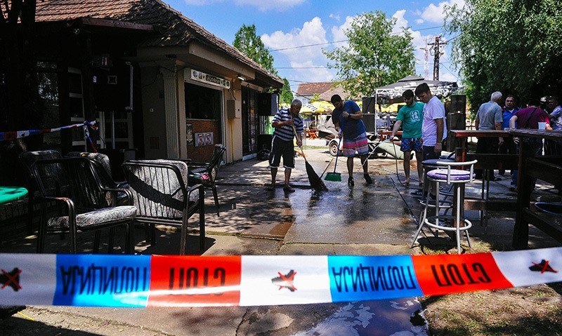 People clean up the ground behind a police ruban at a cafe after a man shot dead five people in the village of Zitiste, northern Serbia on July 2, 2016 (AFP Photo)