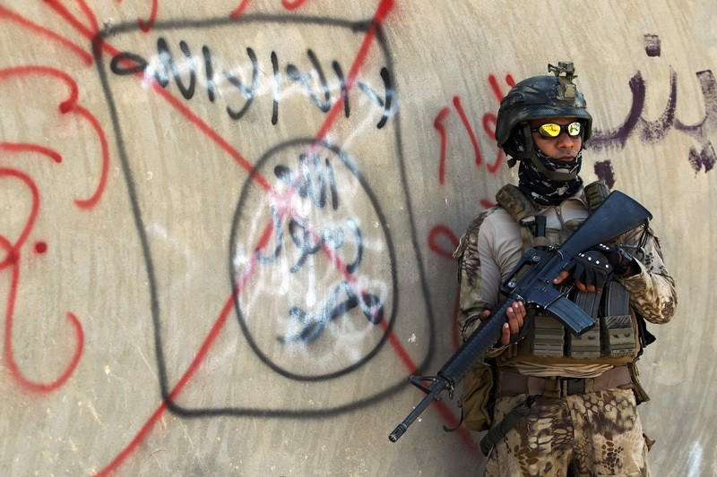 An Iraqi soldier stands next to a wall with a red cross above a slogan of the Daish terrorist group. (AFP Photo)