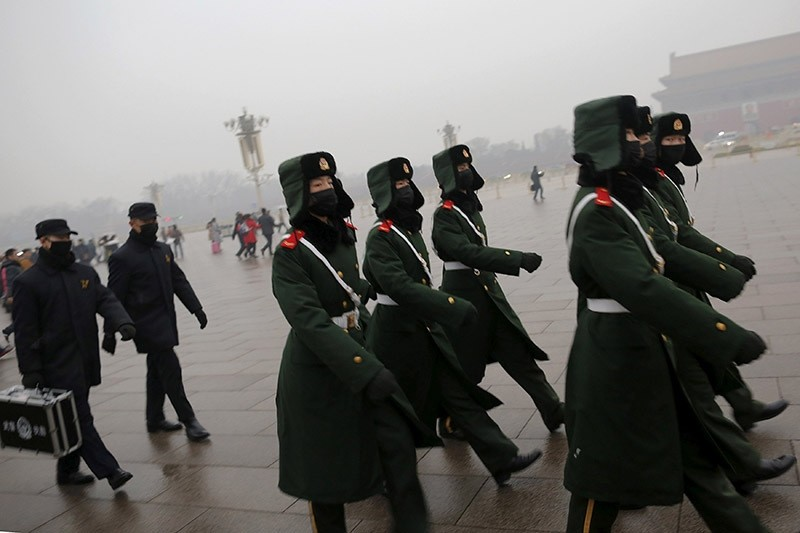 Paramilitary policemen wearing masks march on a cold morning following a flag-raising ceremony amid heavy smog at Tiananmen Square, after the city issued its first ever ,red alert, for air pollution, in Beijing on Dec. 9, 2015. (Reuters Photo)