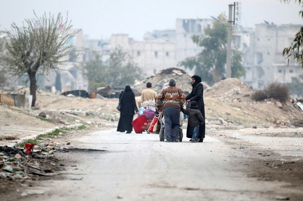 People carry their belongings as they flee the Kadi Askar area towards Bustan al-Qasr neighbourhood, in the opposition-held area of Aleppo, Syria, Dec. 5.