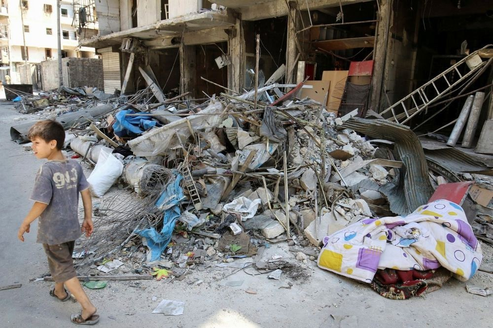 A boy walks past damaged shops in the opposition-held part of Aleppo, frequently targeted by Russia.