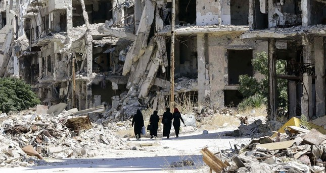 Syrian women walking amid destroyed buildings in the Assad-held Jouret al-Shiah neighborhood of the central Syrian city of Homs on Sept. 19, 2016. (AFP Photo)