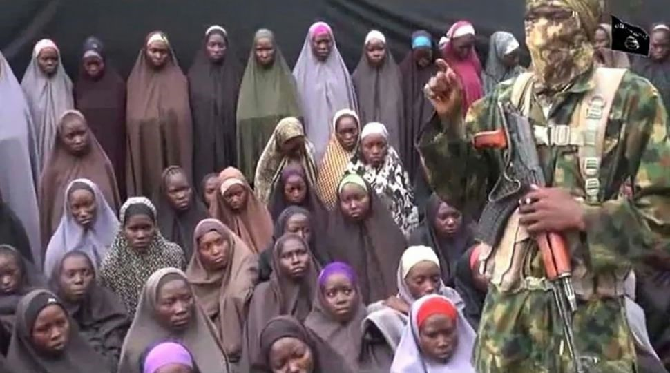 Image taken from a video released on YouTube purports to show a Boko Haram fighter at an undisclosed location in front of girls allegedly kidnapped in April 2014.
