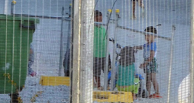 Children play near a fence at the country's Australian-run detention center on the Pacific island nation of Nauru.