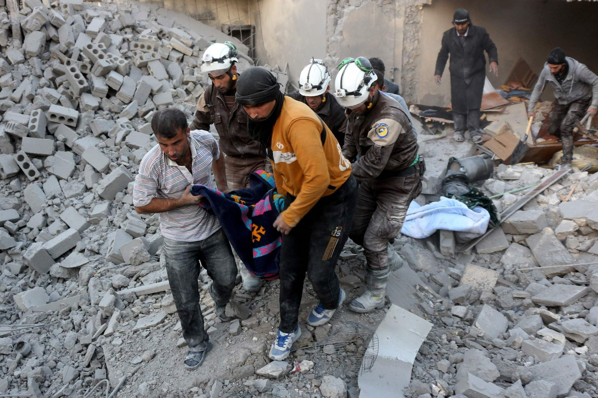 Syrian civil defence volunteers evacuate a victim from the rubble of a building following reported airstrikes on Aleppo's rebel-held district of al-Hamra on November 20, 2016. (AFP PHOTO)