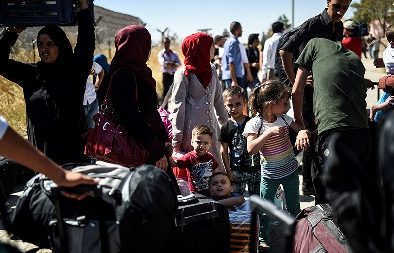 Syrian refugees on their way back to the Syrian city of Jarablus on Sept. 7 at the Karkamu0131u015f crossing gate, in the southern region of Turkeyu2019s Kilis province. (AFP Photo)