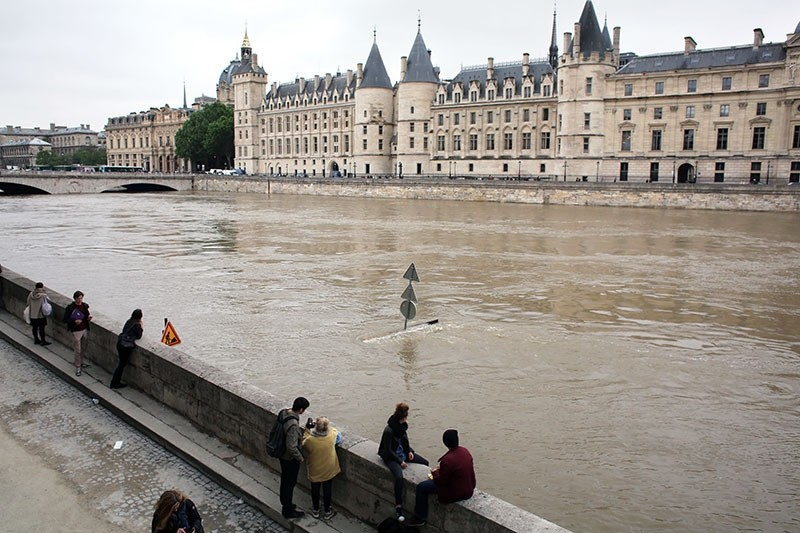 People look at the flooding Seine river, in Paris, Friday June 3, 2016. (AP)