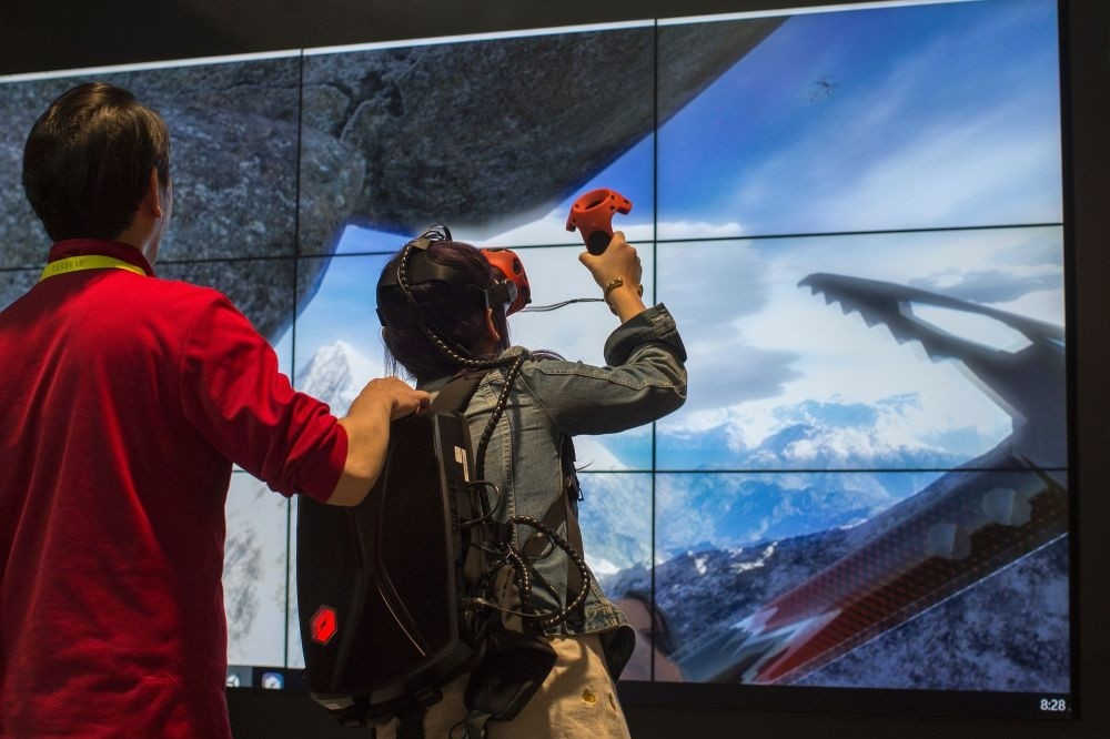 A woman climbs a mountain in a VR experience at the Tsinghua Tongfang exhibit booth during the 2017 Consumer Electronic Show (CES) in Las Vegas.