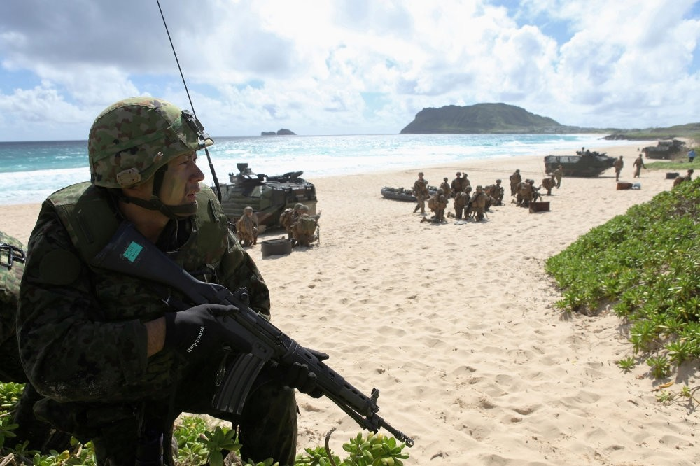 A soldier with the Japan Maritime Self-Defense Force sets up a perimeter defense during a simulated beach assault at Marine Corps Base Hawaii during the multi-national military exercise RIMPAC in Kaneohe, Hawaii.