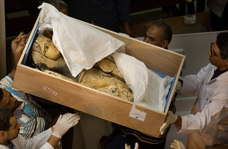 Egyptian antiquities officials carry a lid of a sarcophagus on its arrival to the Egyptian Museum in Cairo, Egypt, Tuesday, June 21, 2016 (AP Photo)