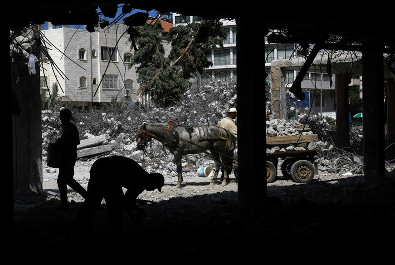 Palestinian workers remove debris from buildings which were destroyed during the 50-day war between Israel and Hamas militants in the summer of 2014, in Gaza City, on August 10, 2016.  AFP Photo