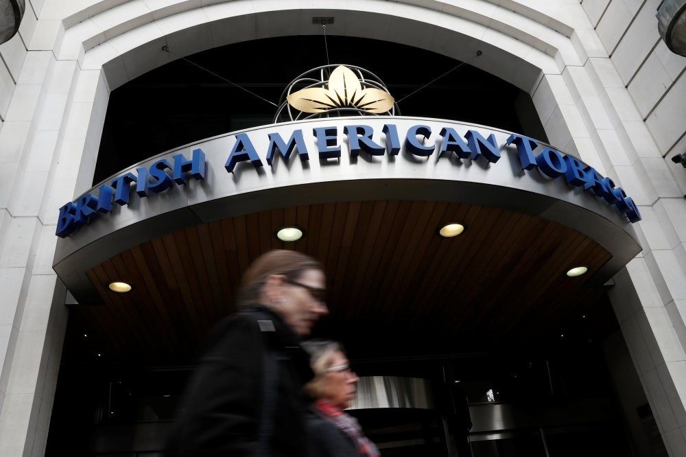 People walk past the British American Tobacco offices in London.