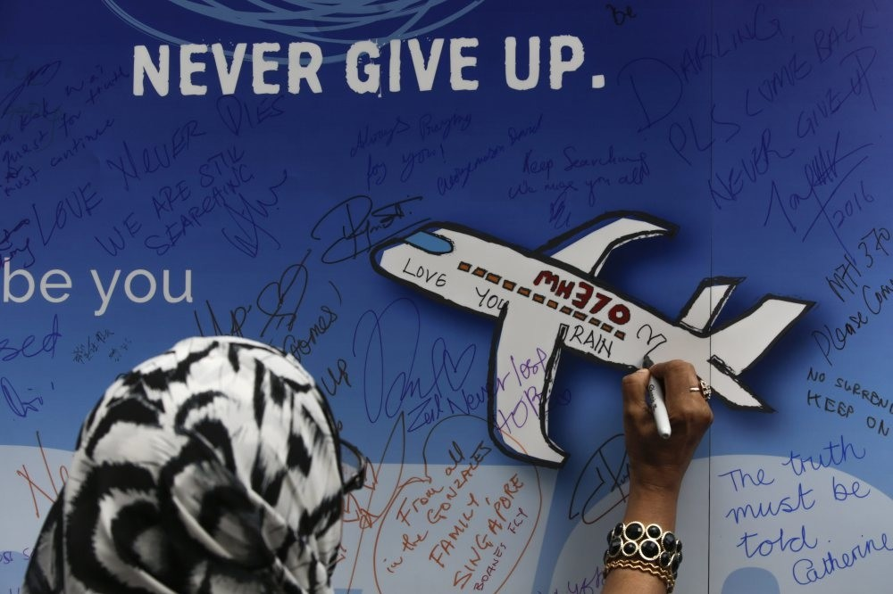 A file picture dated 06 March 2016 shows a woman writing messages for passengers of missing Malaysia Airlines flight MH370 on a banner during a remembrance ceremony to mark the second anniversary of plane's disappearance, in Kuala Lumpur, Malaysia.
