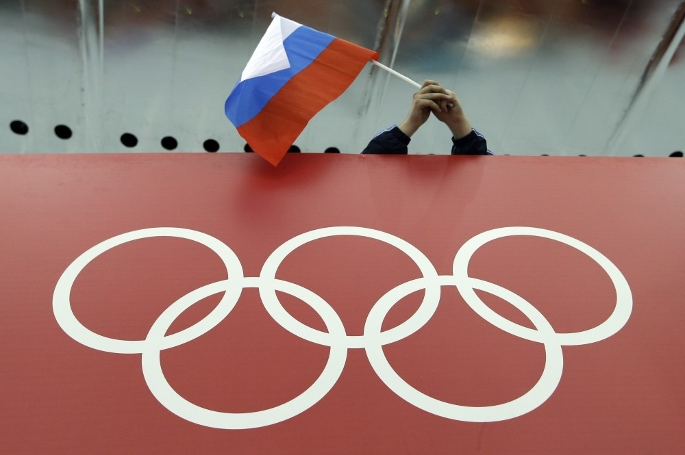 A Russian skating fan holds the countryu2019s national flag over the Olympic rings before the start of the menu2019s 10,000-meter speedskating race during the 2014 Winter Olympics in Sochi, Russia.
