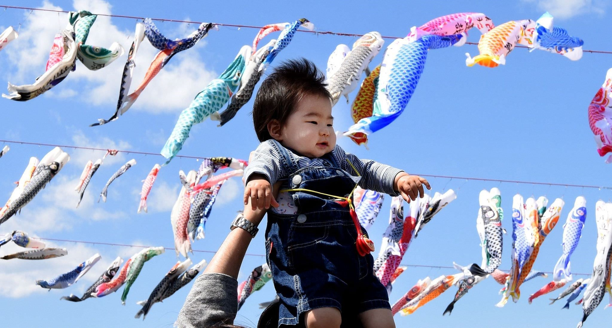 A father holds up his baby under carp streamers fluttering in a riverside park in Sagamihara, suburban Tokyo, on April 29, 2016 ahead of May 5 Children's Day in Japan. (AFP Photo)