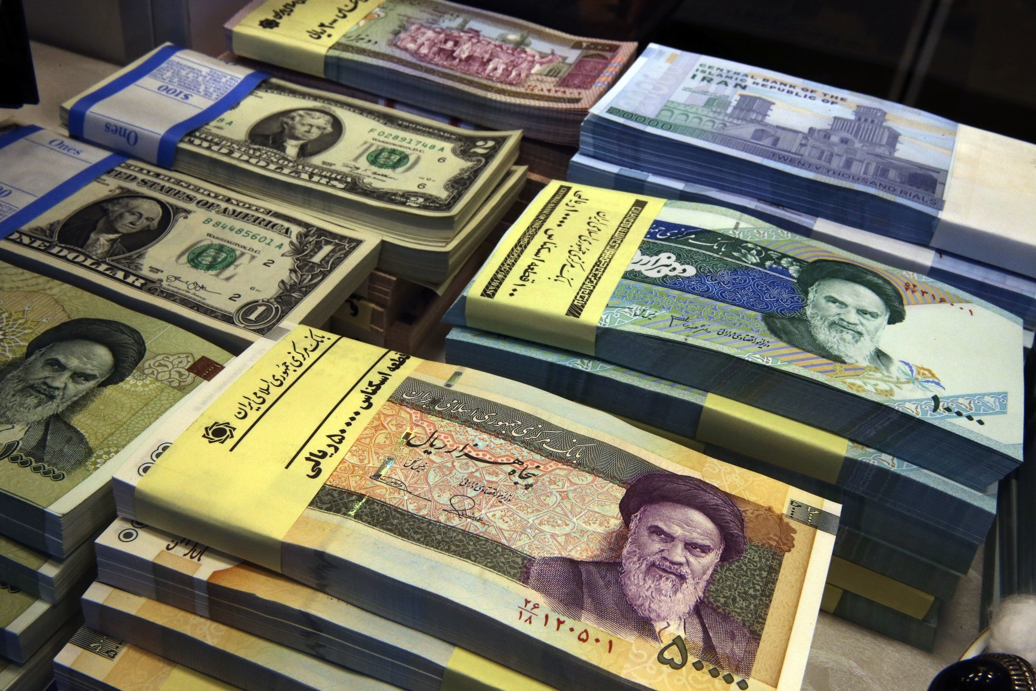 In this April 4, 2015 photo, Iranian and U.S. banknotes are on display at a currency exchange shop in Tehran, Iran. (AP Photo)
