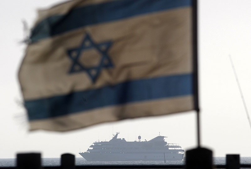 An Israeli flag flutters in the wind as a naval vessel (not seen) escorts the Mavi Marmara that was raided by Israeli marines, to the Ashdod port, in this May 31, 2010 file picture. (Reuters)