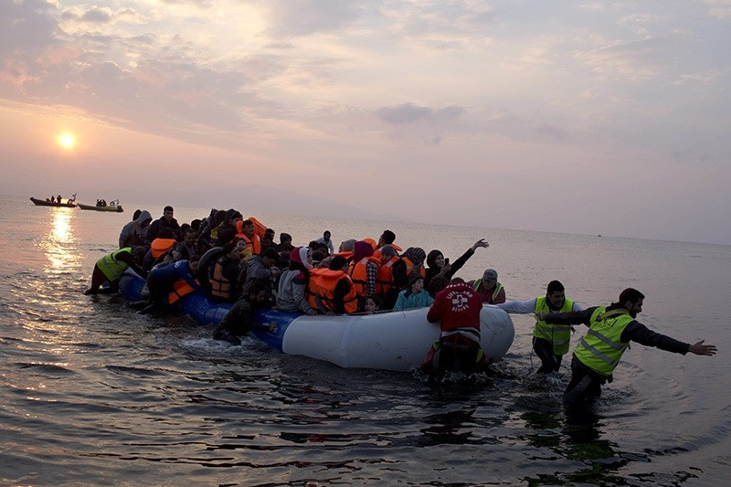 Refugees on a dingy as they arrive at the shore of the northeastern Greek island of Lesbos, after crossing the Aegean sea from Turkey, March 20, 2016. (AP Photo)