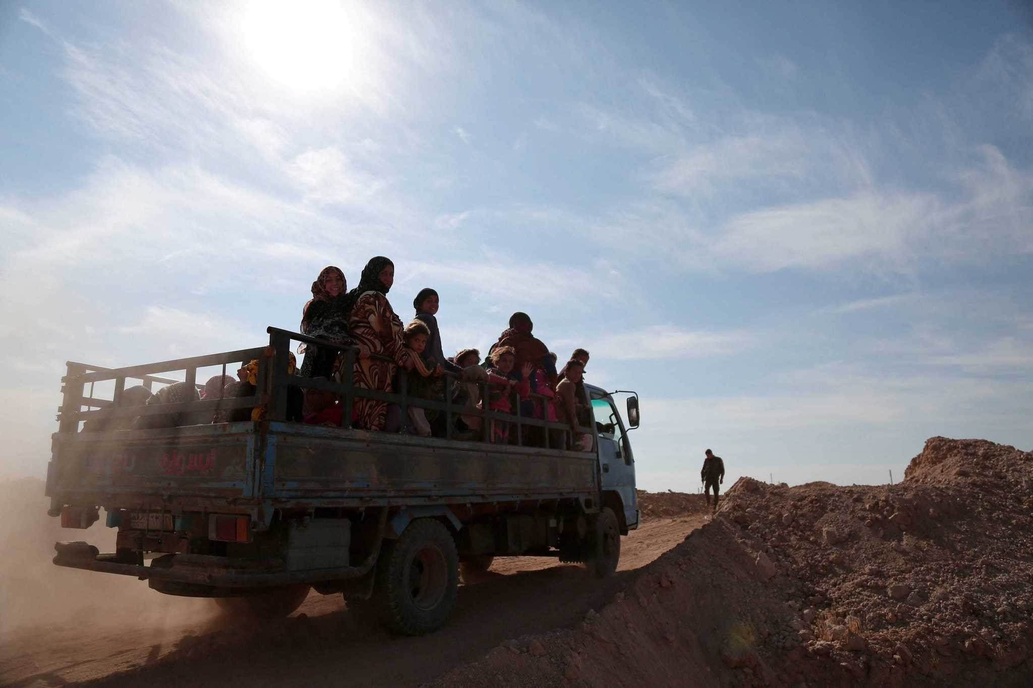 People fleeing areas of conflict ride a vehicle, north of Raqqa city, Syria, Nov. 8, 2016.