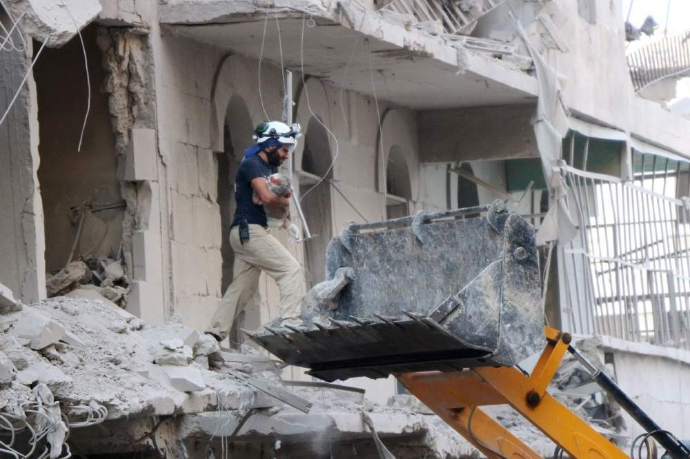 A Syrian rescue worker removes the body of an infant from the rubble of a damaged building following reported Assad regime air strikes on July 7.