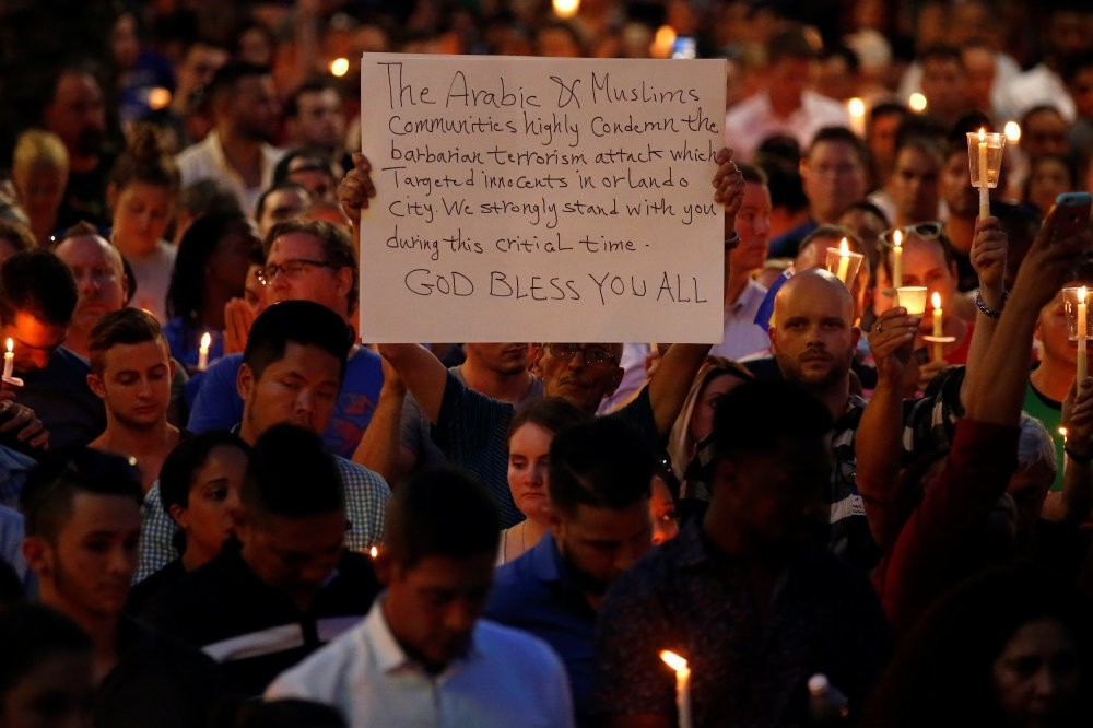 People take part in a candlelight memorial service day after the mass shooting at a nightclub in Orlando, Florida, June 13.