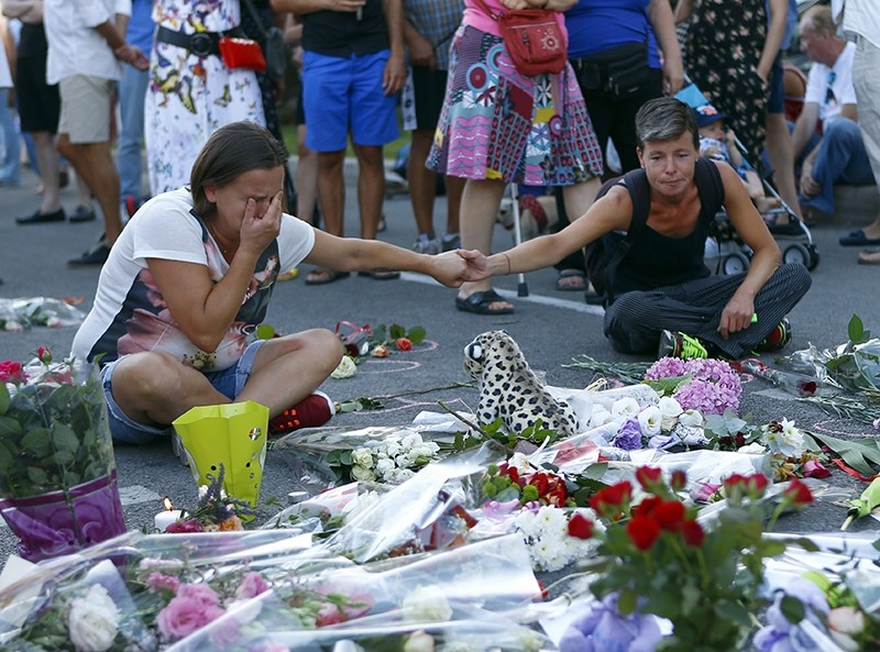 People pay tribute to the victims at the site of a deadly truck attack on the famed Promenade des Anglais in Nice, southern France, Saturday, July 16, 2016. (AP Photo)
