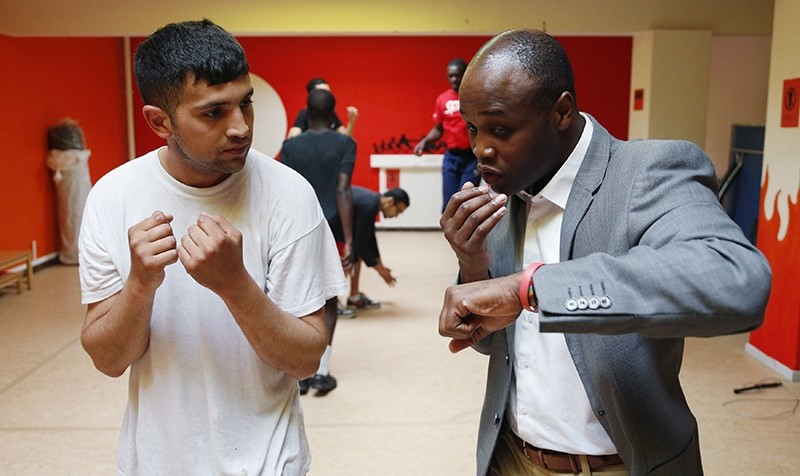 Former Belgian boxing champion Bea Diallo gives instructions to unemployed Mohamed Sammar (L) during a ,Fit for a job, boxing class in Brussels July 5, 2013 (Reuters Photo)