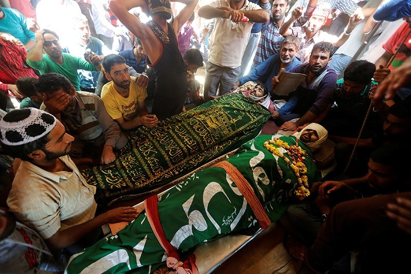 Kashmiri villagers sit next to the bodies of civilians, who according to local media were killed during clashes between police and protesters, during their funerals in Beerwah, north of Srinagar, August 16, 2016. (Reuters Photo)