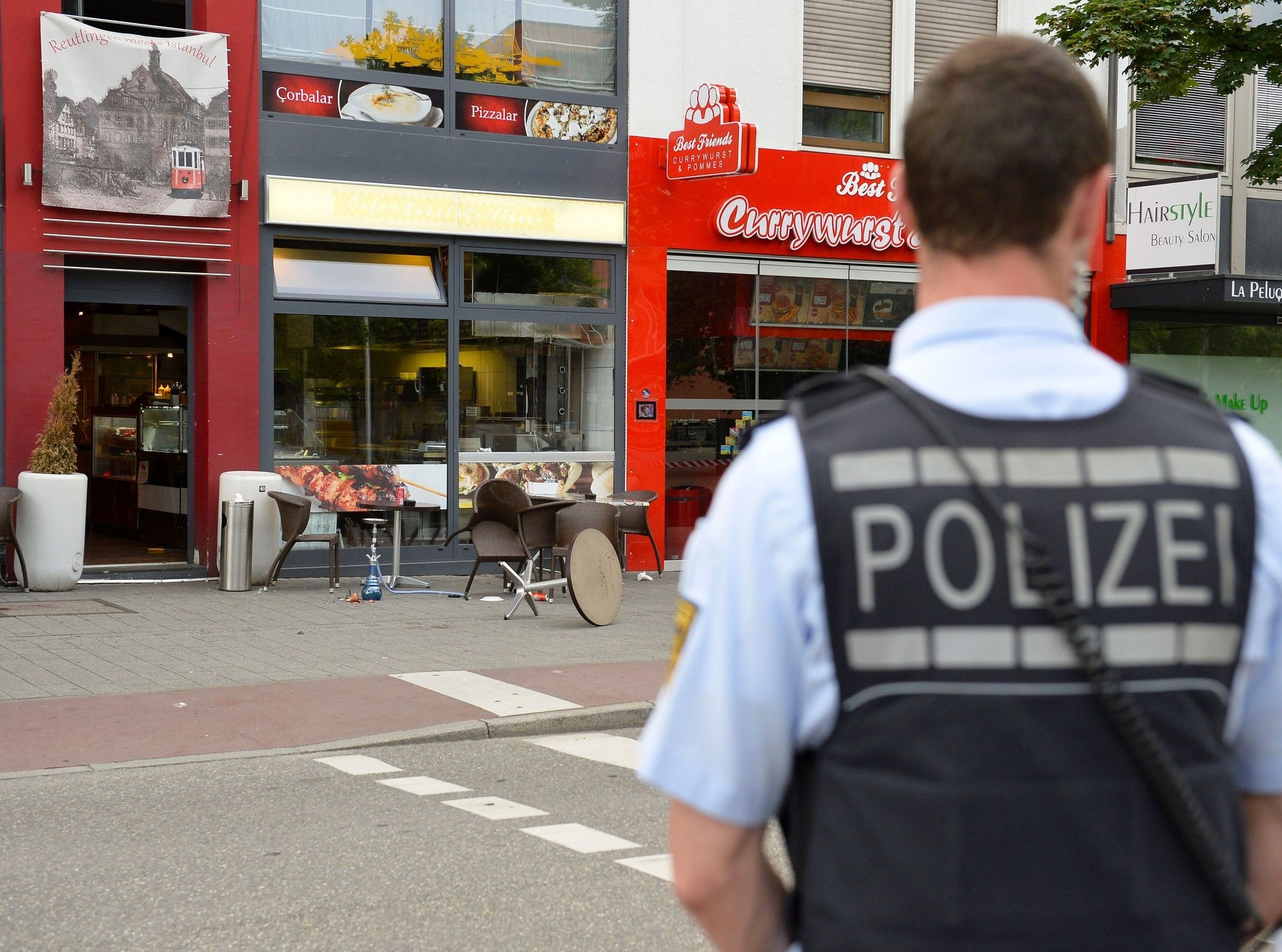 A police officer stands in front of a fastfood restaurant in Reutlingen, southwestern Germany, on July 24, 2016 where a Syrian asylum-seeker killed a woman and injured two people with a machete. (AFP Photo)