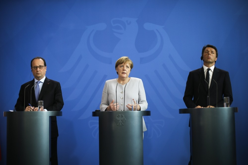 France's President Franu00e7ois Hollande, (L), German Chancellor Angela Merkel, (C) and the Prime Minister of Italy Matteo Renzi, (R), brief the media during a meeting at the chancellery in Berlin on June 27.