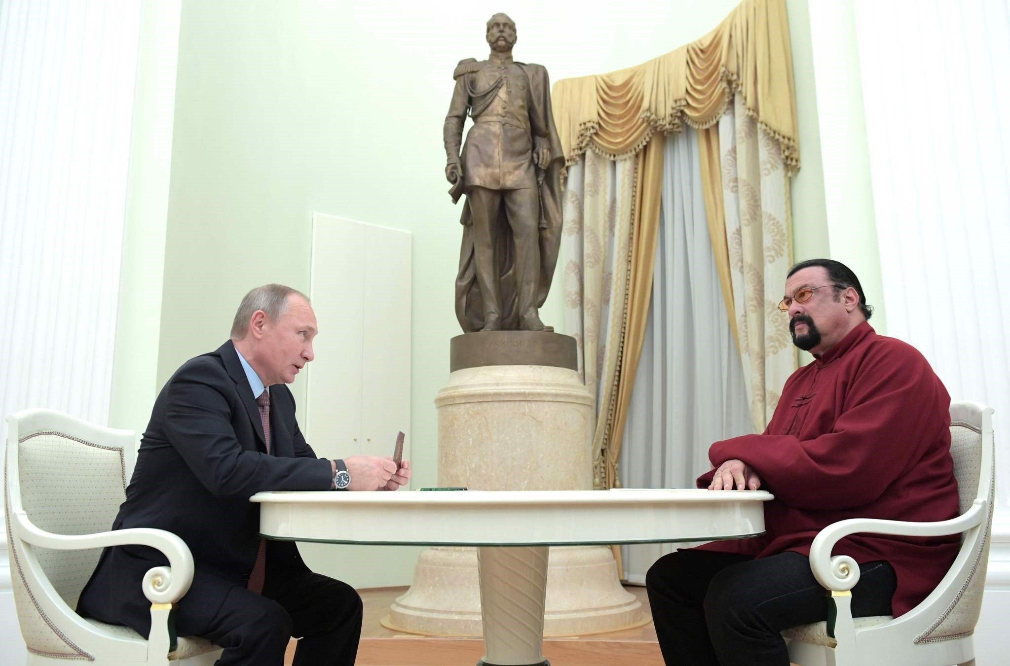 Putin (L) holds a Russian passport before presenting it to US action hero actor Steven Seagal during a meeting at the Kremlin in Moscow on Nov. 25, 2016. (AFP Photo)