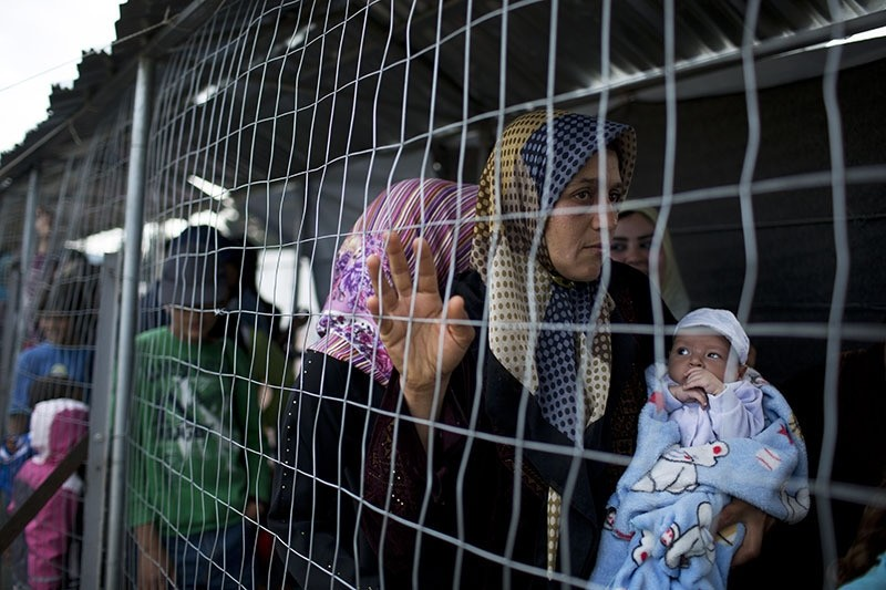 Syrian woman holds 9 days old baby who was born in the camp as refugees  queue to receive food at the northern Greek border point of Idomeni, Greece, May 10, 2016. (AP)