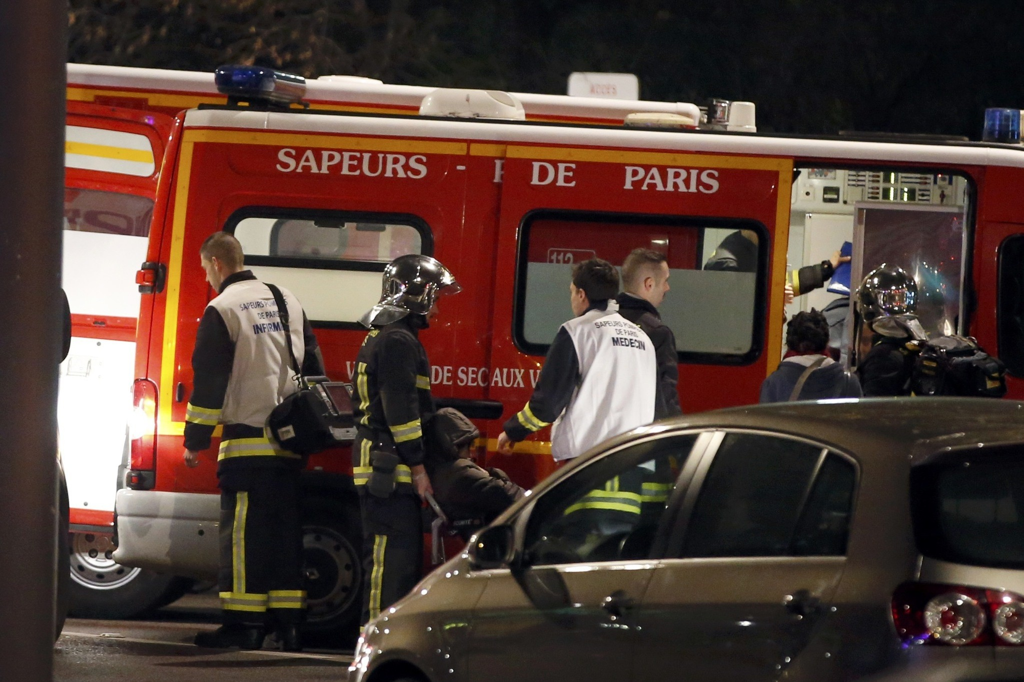 French firemen and doctors tend to a person who was one of six people in a travel agency when an armed man entered in what appears to be a robbery. (REUTERS Photo)