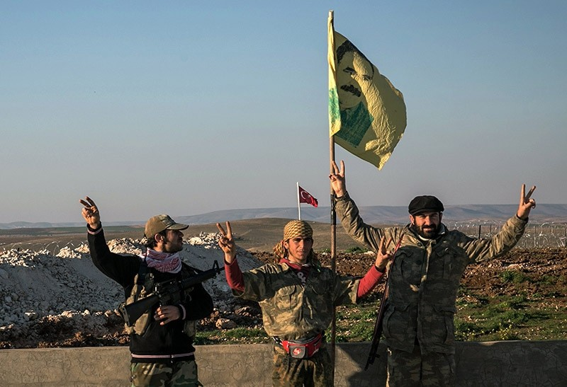 In this Feb. 22, 2015 file photo, YPG terrorists make a V-sign next to a drawing of Abdullah u00d6calan, jailed PKK leader, in Esme village in Aleppo province, Syria. (AP Photo)