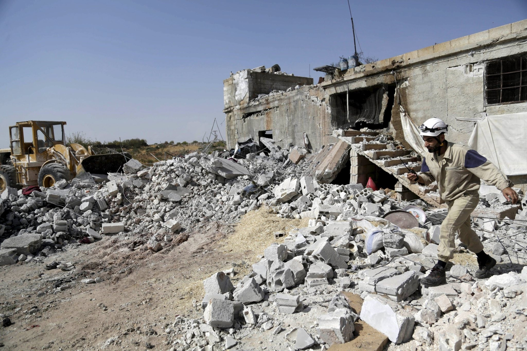A civil defence member walks on the rubble of a damaged building next to a site hit by what activists said were airstrikes carried out by the Russian air force. (Reuters Photo)