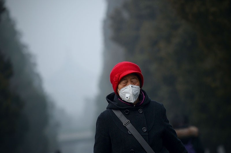 An elderly woman wearing a mask closes her eyes, as she walks at a park in Beijing on December 20, 2016. (AFP Photo)