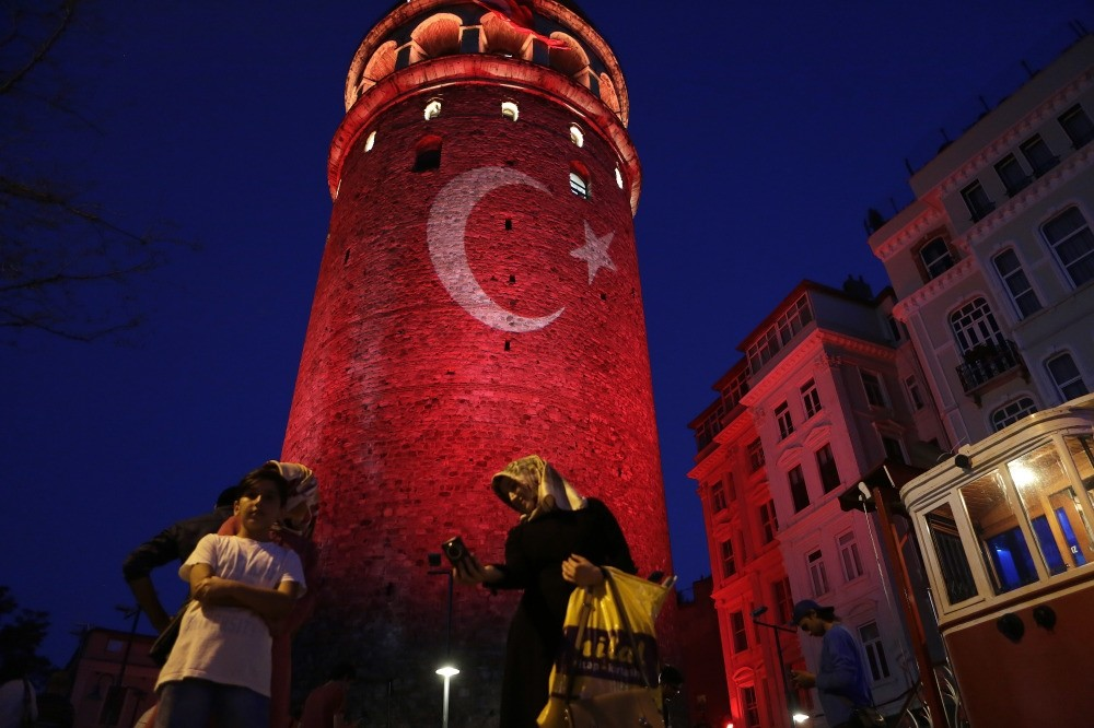 People taking photos at the iconic Galata Tower, illuminated in the colors of the Turkish flag to protest the coup attempt, Istanbul, July 30.