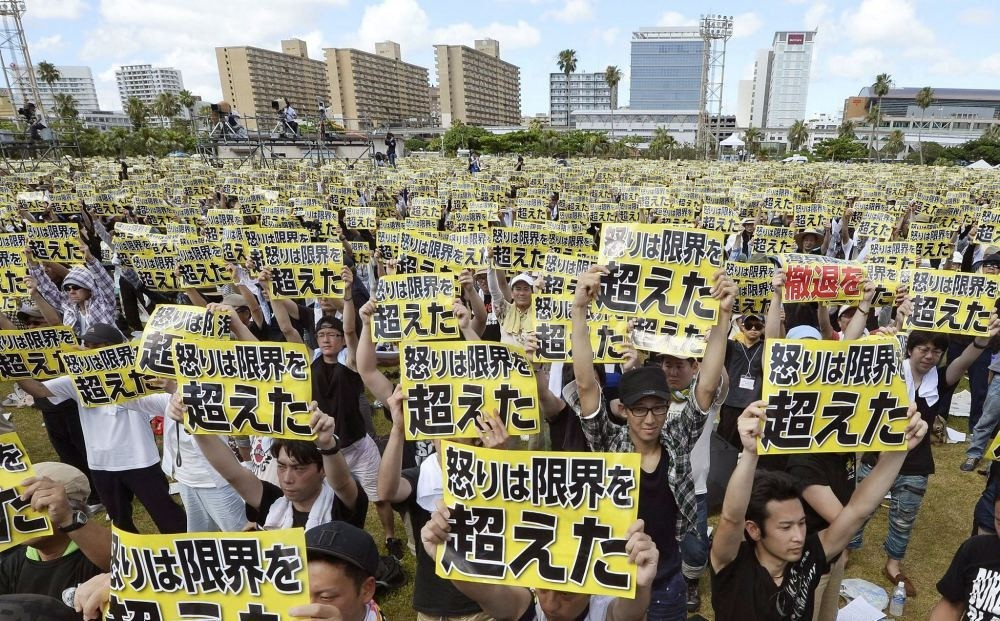 Protesters hold placards that read: ,Our anger has reached its limit, during a protest rally against the presence of U.S. military bases.