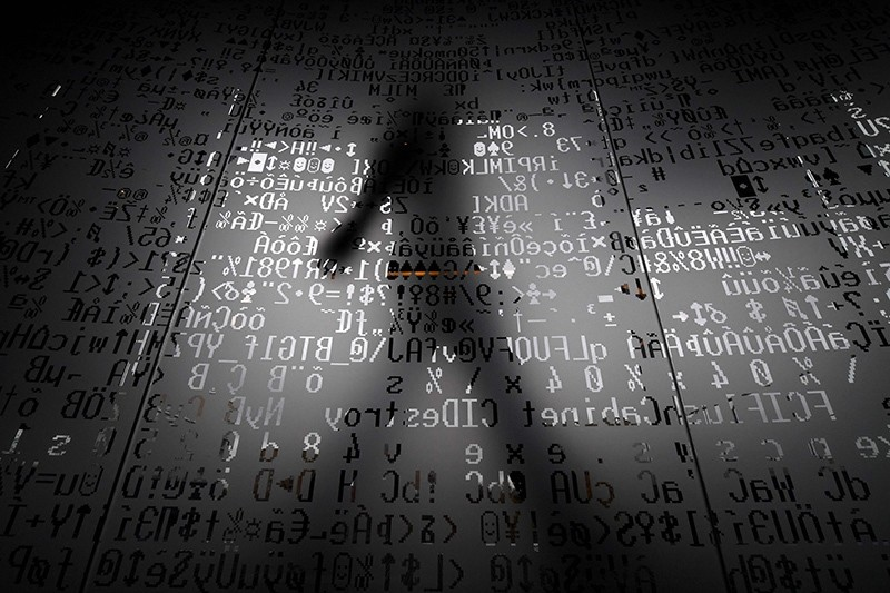 A picture taken on October 17, 2016 shows an employee walking behind a glass wall with machine coding symbols at the headquarters of Internet security giant Kaspersky in Moscow. (AFP Photo)