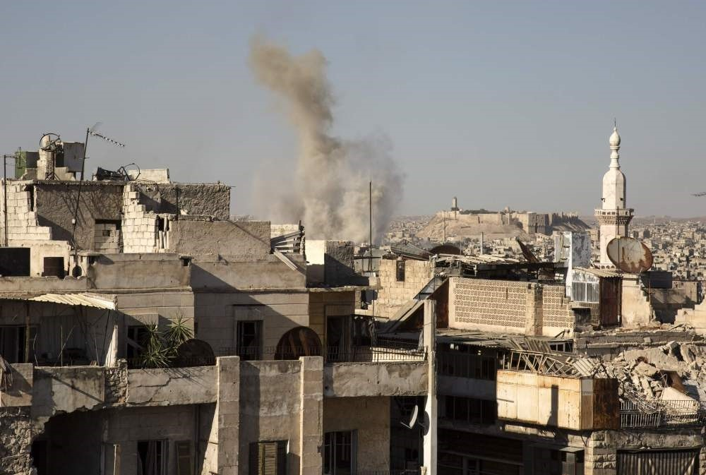 Smoke billows up following a reported strike by regime forces in an opposition-held neighborhood in the northern city of Aleppo, July 12.